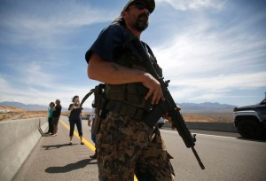A protester carries a rifle on a bridge next to the Bureau of Land Management's base camp where seized cattle, that belonged to rancher Cliven Bundy, are being held at near Bunkerville