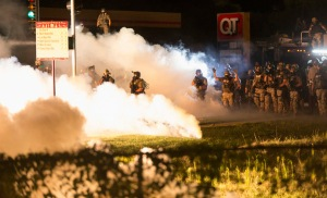 Riot police clear a street with smoke bombs while clashing with demonstrators in Ferguson, Missouri