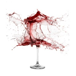 Explosion of a glass with red wine on a white background
